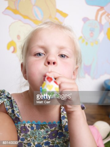 Young Girl blowing noise maker : Stock Photo