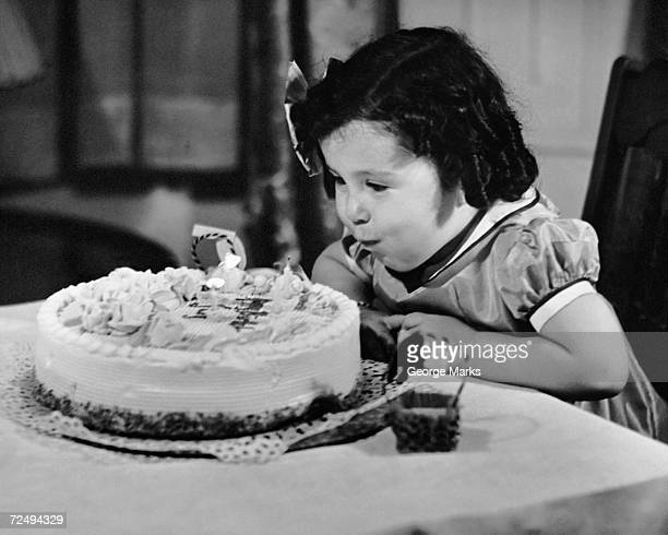 Young girl blowing out candles on cake