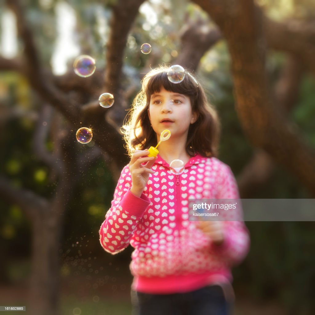 Young Girl Blowing Soap Bubbles : Stock Photo