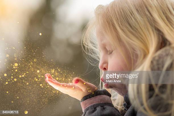 Young girl blows glitter into the air