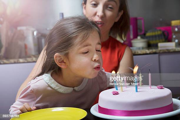 Young girl blows out candles on birthday cake.