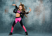 Young girl break dancing on gray wall stidio background.