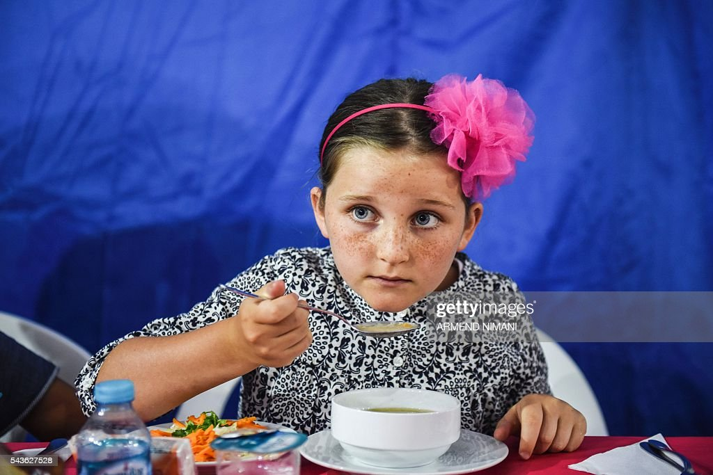 A young girl breaks the fast with a dinner distributed for free during the Muslim fasting month of Ramadan on June 29, 2016 in Pristina. Muslims fasting in the month of Ramadan must abstain from food, drink and sex from down to dusk, when they break the fast with meal known as iftar. / AFP / ARMEND