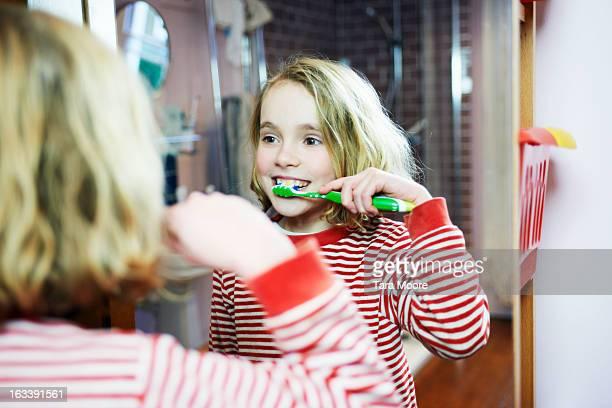 young girl brushing teeth in bathroom mirror