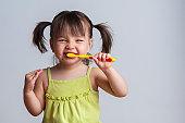 Toddler smiling while brushing her teeth
