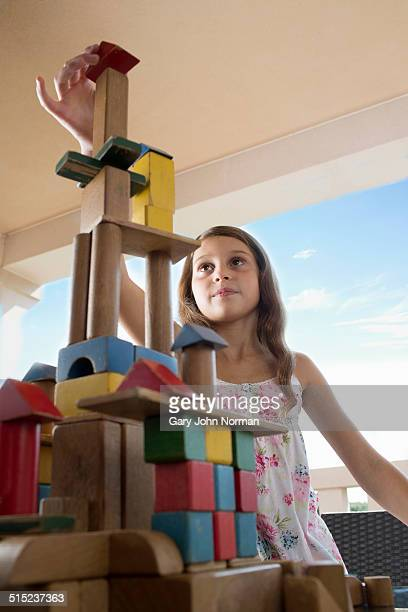 Young girl building a tower with wooden bricks