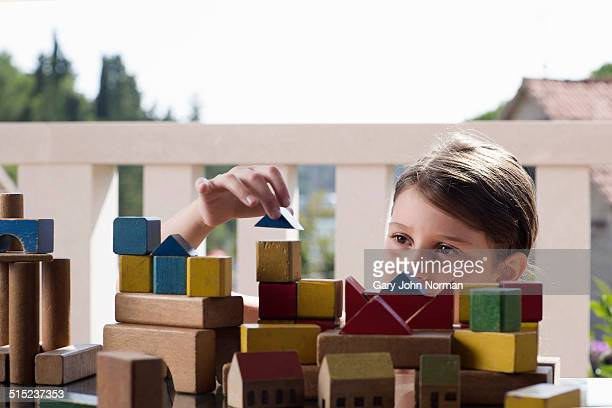 Young girl building a town with wooden bricks
