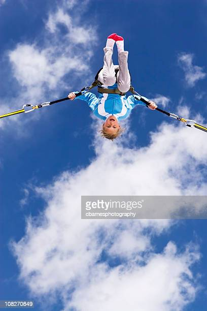 young girl bungee jumping up to clouds in blue sky