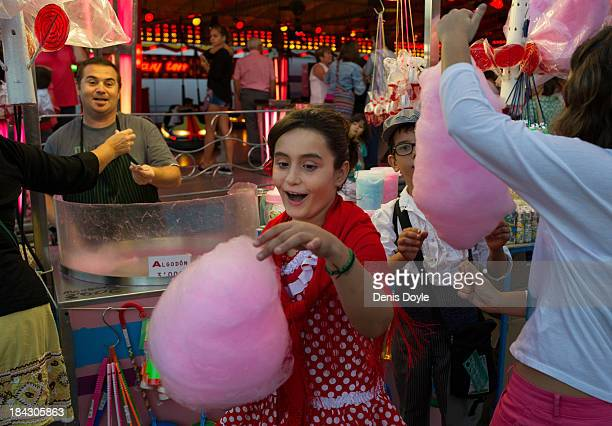 A young girl buys cotton candy or candy floss during the weeklong Lady Of The Rosary Festival on October 12 2013 in Fuengirola Spain The Fuengirola...