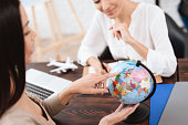 A young girl came to a travel agency. She wants to make journey. The travel agent helps her.