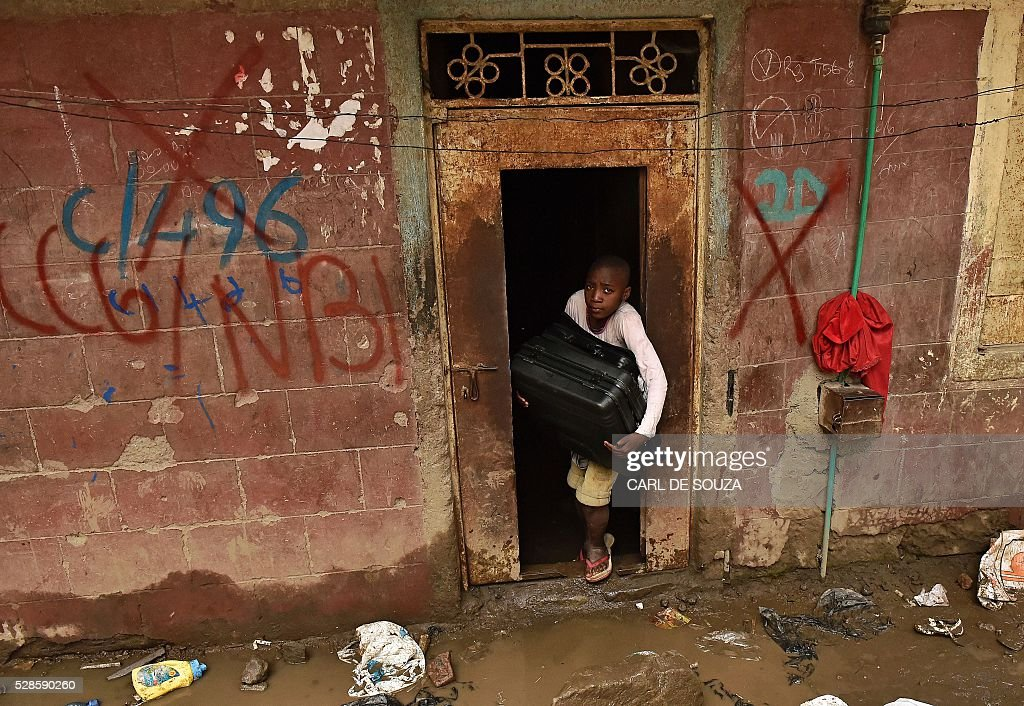 A young girl carries a suitcase from a block of flats which is going to be demolished on May 6, 2016. Following a building collapse which claimed at least 40 lives with more 80 people still unaccounted for, after severe flooding, the government has ordered the demolition of similar unsafe buildings in the area. Located in the poor, tightly-packed Huruma neighbourhood, the building, which housed around 150 families crammed into single rooms, had been slated for demolition after being declared structurally unsound. But an evacuation order for the structure, which was built next to a river just two years ago, was ignored. AFP PHOTO/Carl de Souza Following a building collapse which claimed at least 40 lives with more 80 people still unaccounted for, after severe flooding, the government has ordered the demolition of similar unsafe buildings in the area. Located in the poor, tightly-packed Huruma neighbourhood, the building, which housed around 150 families crammed into single rooms, had been slated for demolition after being declared structurally unsound. But an evacuation order for the structure, which was built next to a river just two years ago, was ignored. / AFP / CARL