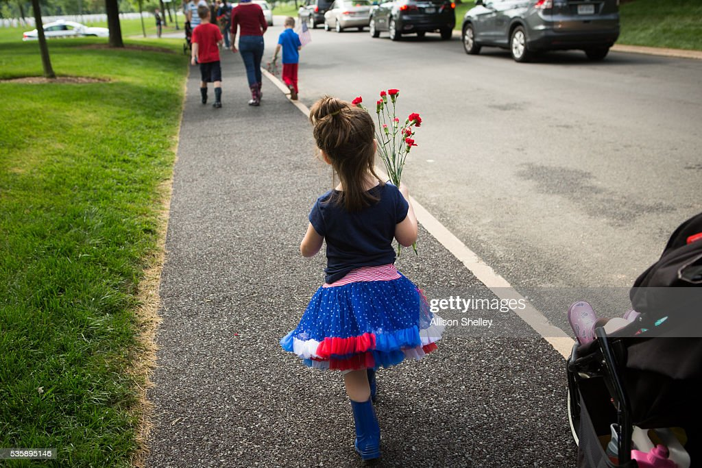 A young girl carries flowers to place on a grave at Arlington National Cemetery on May 30, 2016 in Arlington, Virginia.