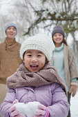 Young girl carrying snow balls in front of parents in park in winter