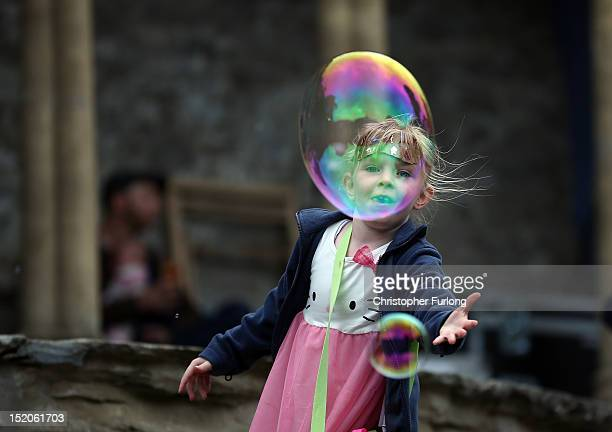 A young girl catches giant soap bubbles during The Number Six Festival on September 15 2012 in Porthmadog United Kingdom The classic Italianate...