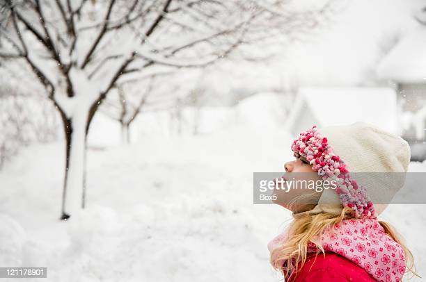Young girl catching a snowflake