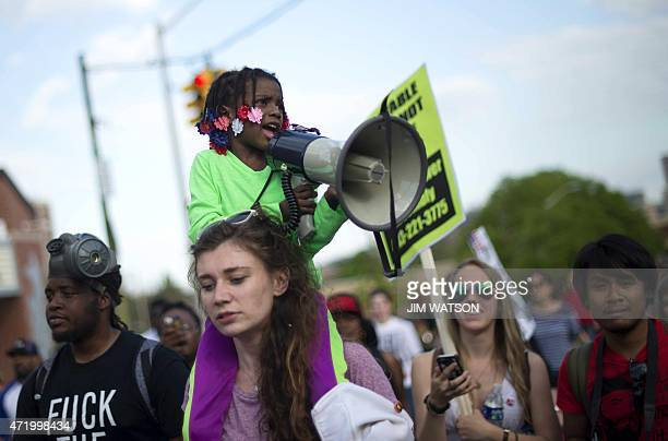 A young girl chants in a megaphone as she rides on the shoulders of a demonstrator during a protest march in Baltimore Maryland May 2 2015 Thousands...