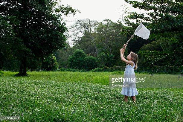 young girl chasing butterflies with net