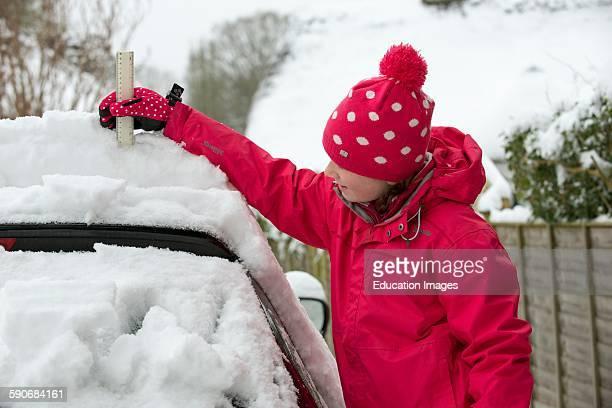 Young girl checks the snow depth on a car using a ruler