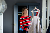 Young girl choose a dress at home near wardrobe in bedrood. interior in Dutch style