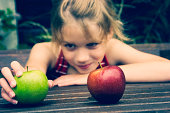 Young girl choosing an apple