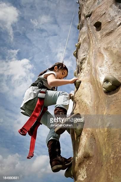 Young Girl Climbing Rock Wall
