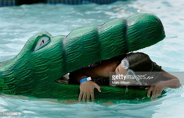 A young girl climbs into the mouth of an aligator float at the Chesapeake Beach Water Park July 31 2006 in Chesapeake Beach Maryland Temperatures in...