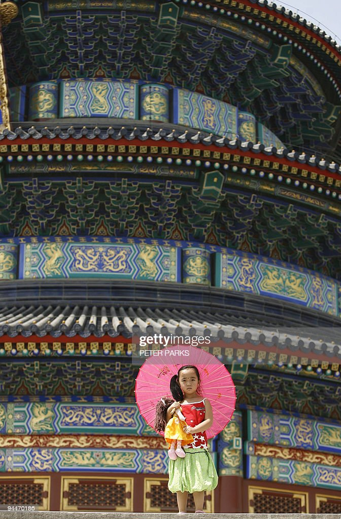 A young girl clutches her doll whilst visiting the Temple of Heaven in Beijing 29 May 2007. More than 20 percent of toys made in China for its domestic market are substandard or potentially dangerous, state media said in the latest example of the country's lax consumer-product controls. AFP PHOTO/Peter PARKS