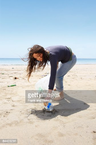 Young girl collecting garbage on beach