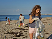 Young girl collecting trash on beach, team in back