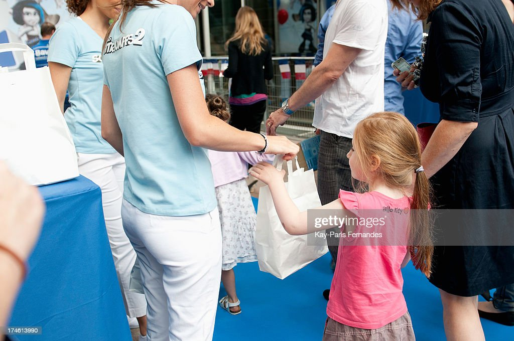 A young girl collects her gift bag at the 'Smurfs 2' Paris Premiere at UGC Cine Cite Bercy on July 28, 2013 in Paris, France.