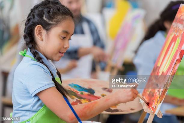 Young girl concentrates while painting in art class
