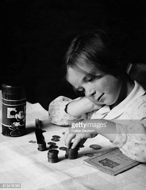 A young girl counts the pennies she has collected for deposit in her savings bank as her contribution to the war effort