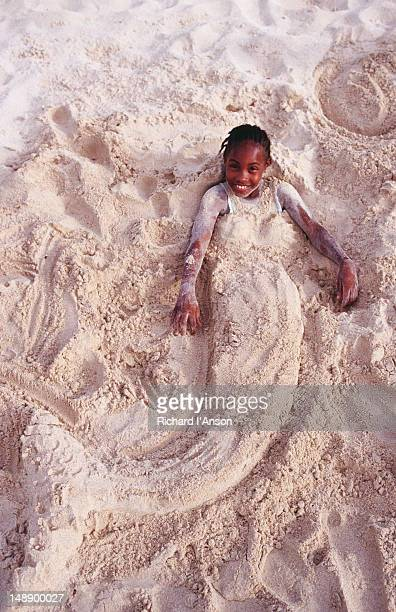 Young girl covered with sand in mermaid shape on Grand Anse Beach.