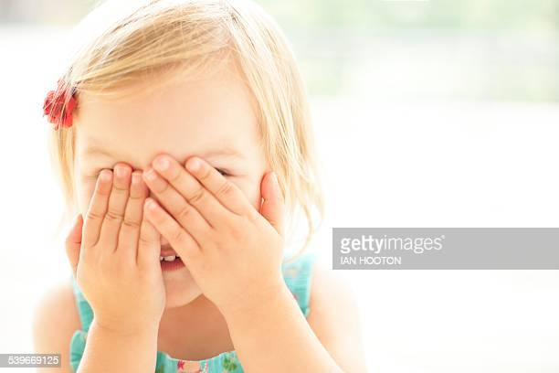 Young girl covering face with hands