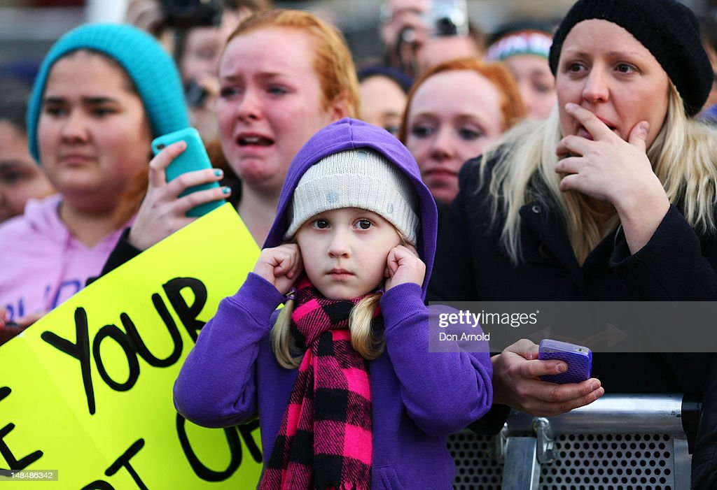 A young girl covers her ears against the deafening screams of fans as Justin Bieber performs live on the Sunrise program at The Overseas Passenger Terminal on July 18, 2012 in Sydney, Australia.