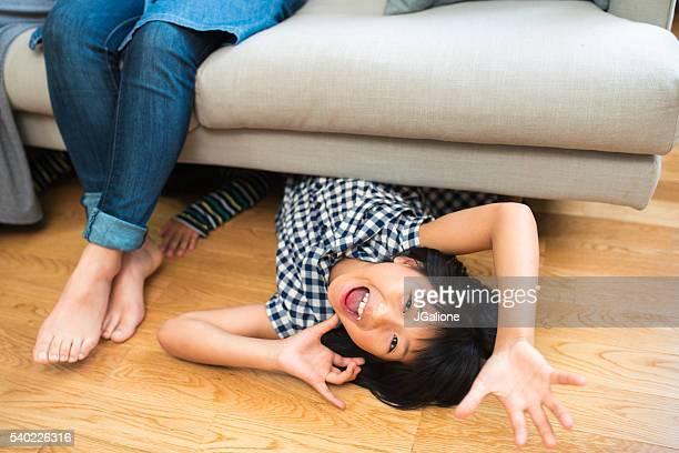 Young girl crawling out from under the sofa