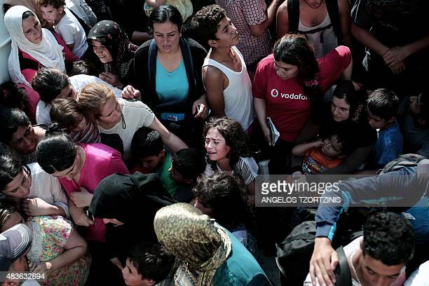 A young girl cries as migrants wait to be registered at the stadium on the Greek island of Kos on August 11 2015 Police on the Greek island of Kos...