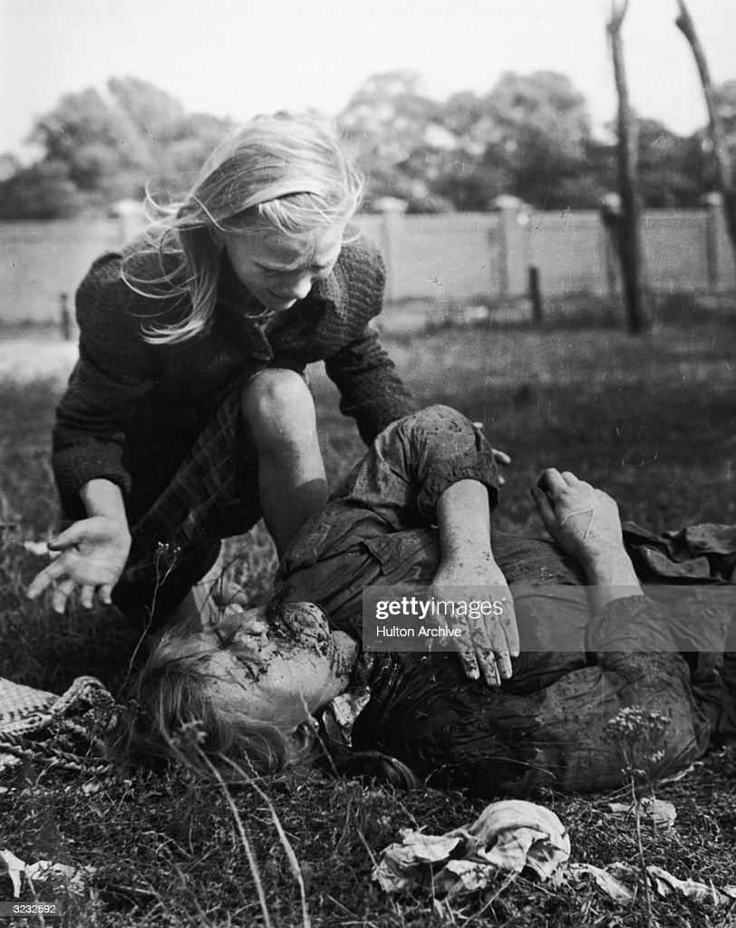 A young girl cries over her wounded and bleeding sister who lies on the ground with her hand covered over a chest wound during the Nazi invasion of...