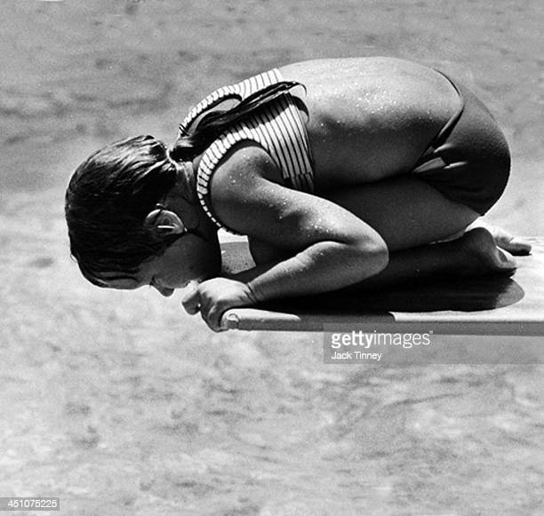 A young girl crouches at the end of a diving board and peers down into a swimming pool 1968