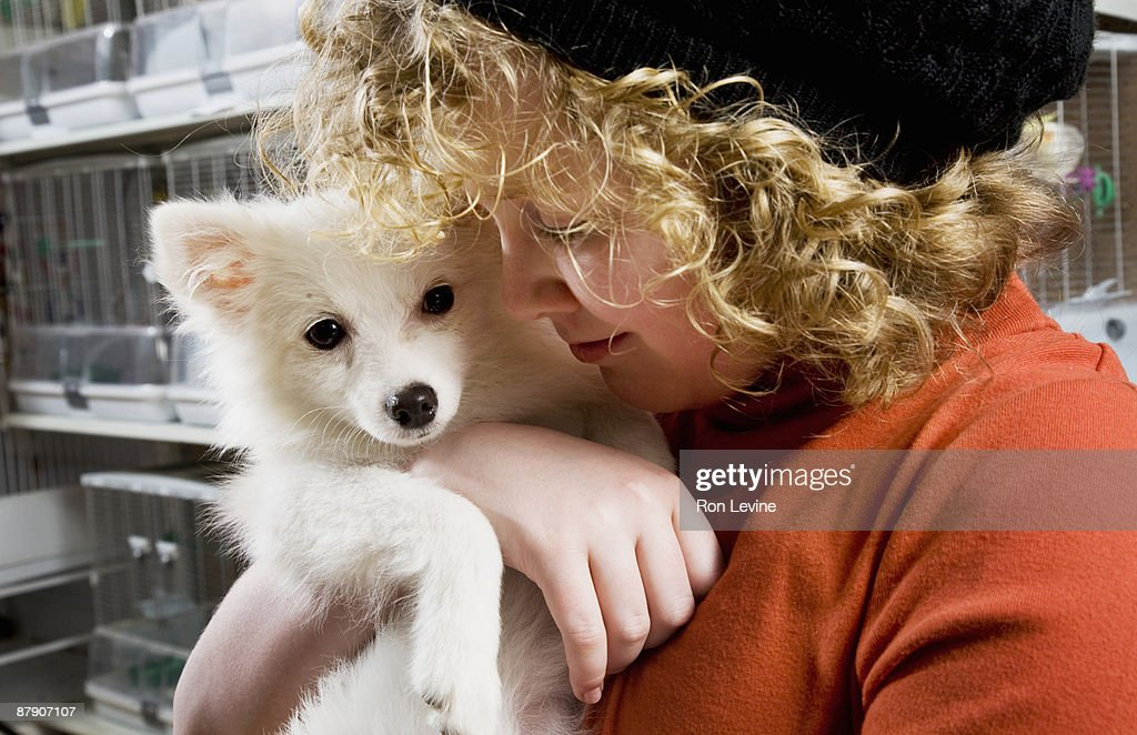 Young girl cuddling a puppy in a pet shop : Stock Photo