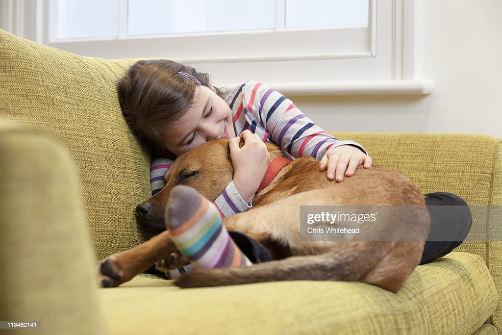 Young girl cuddling her dog on the sofa : Stock Photo