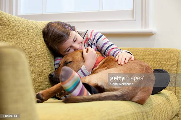 Young girl cuddling her dog on the sofa