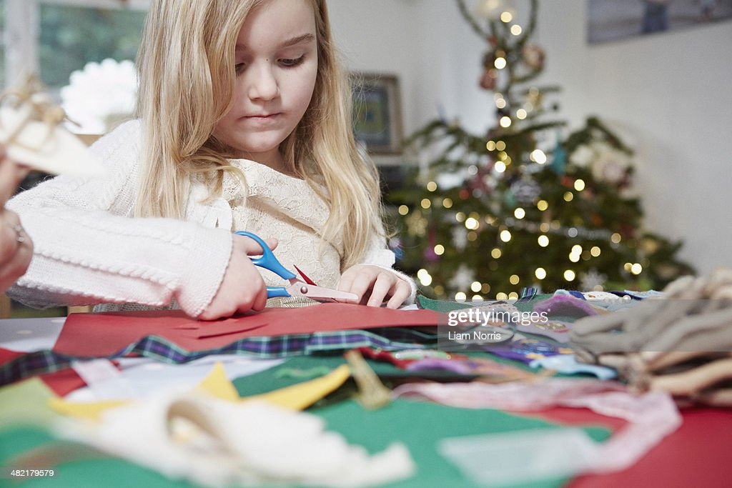 Young girl cutting out paper with scissors : Stock-Foto