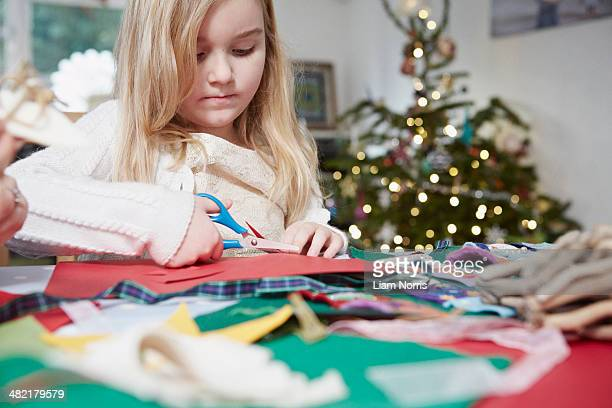 Young girl cutting out paper with scissors