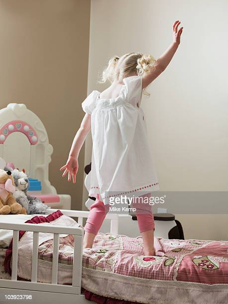 Young girl dancing on her bed