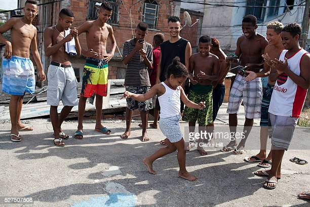 Young girl dancing passinho to funk Carioca Baile funk with a group of young men guys on a rooftop Vila Valquiere West Zone Zona Oueste Rio de Janeiro