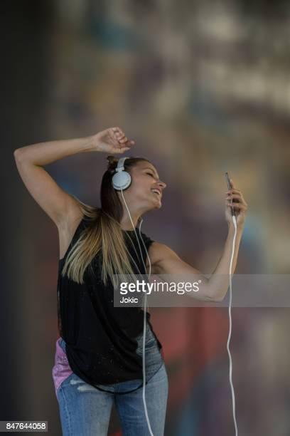 Jeune fille de danser sur la musique de smartphone