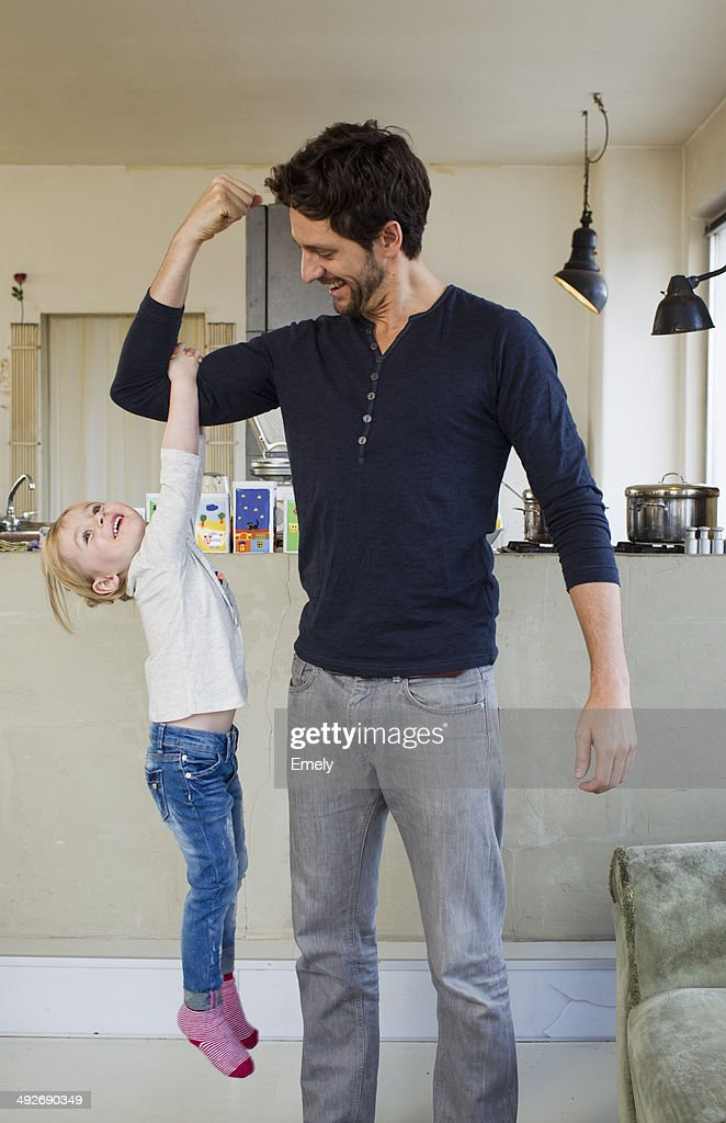 Young girl dangling from her fathers arm