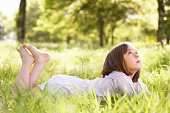 Young Girl Daydreaming Lying In Summer Field