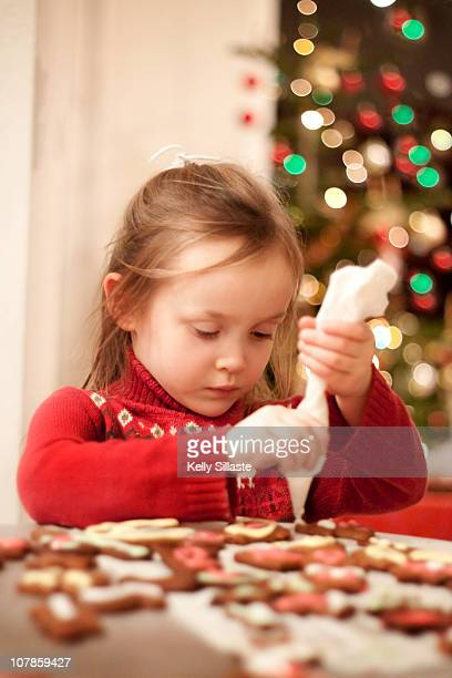 A young girl decorating Christmas cookies